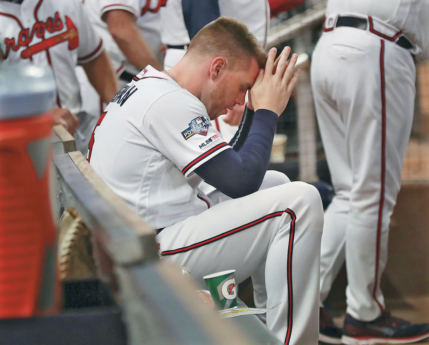 ATLANTA BRAVES first baseman Freddie Freeman sits in the dugout in the ninth inning of the team's 13-1 loss to the St. Louis Cardinals in Game 5 of the National League Division Series Wednesday, in Atlanta.