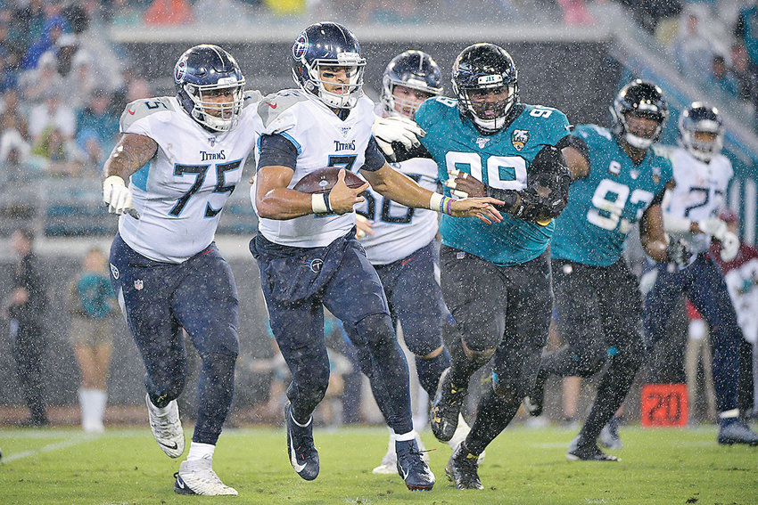 TENNESSEE TITANS quarterback Marcus Mariota (8) scrambles for yardage in front of Jacksonville Jaguars defensive tackle Marcell Dareus (99) in the first half in Jacksonville, Fla.