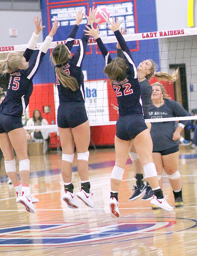 WALKER VALLEY middle hitter Melody McRee (back) finds the going tough as a trio of Cookeville players meet her at the net during Monday evening's Region 3-AAA semifinal at Raider Arena.