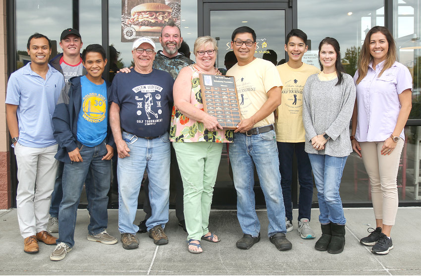KIM AND DANNY LEDFORD, fourth and third from left, present a plaque to Shane's Rib Shack employees listing winners of the Dustin Ledford Foundation scholarships. Their son, Dustin Ledford, was killed by an alcohol-impaired motorist in 2010. Tuesday would have been Dustin's 34th birthday. Front row, from left, are Binh Morris, Francisco Davis, Danny Ledford, Kim Ledford, Shane's Rib Shack owner Michael Aseron, Jackson Aseron, Shane's Rib Shack owner Julie Aseron and Sarah Davis. Standing in the back row are Easton Clark and Aaron Vaught.