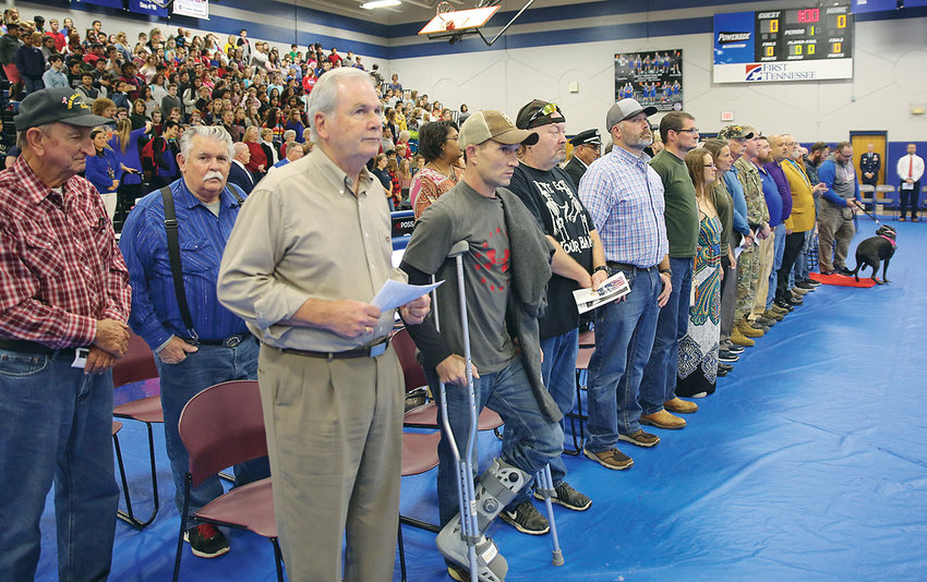 MILITARY VETERANS attending the Cleveland Midle School Veterans Day program stand as they are recognized on Monday.