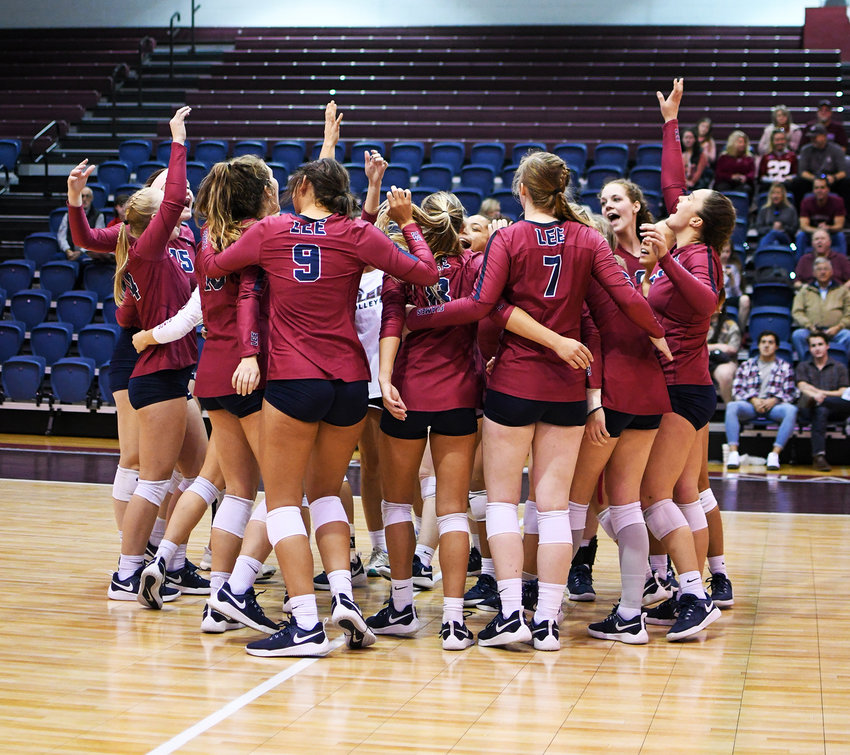 THE LEE LADY FLAMES celebrate after wrapping up the volleyball season with a 3-1 win over Christian Brothers Saturday, in Walker Arena.