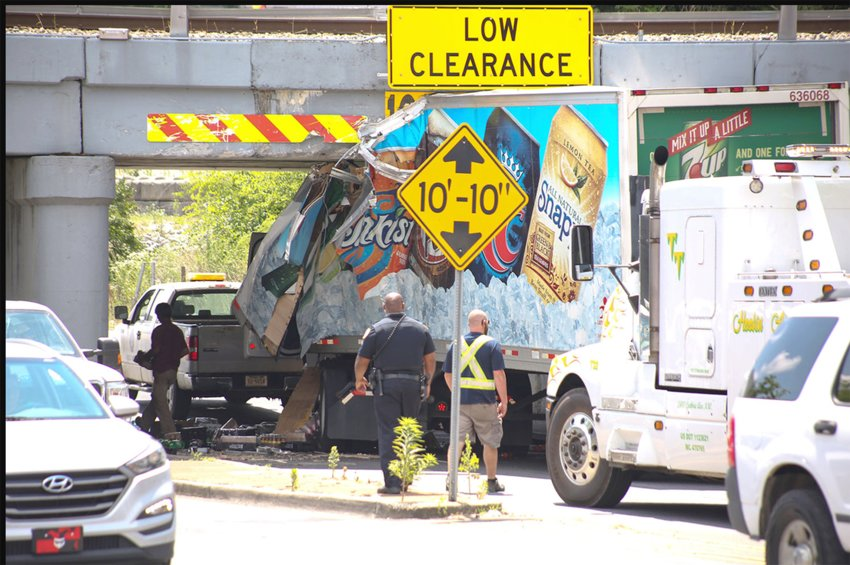 TWO VEHICLES that were pinned last month under the Norfolk Southern bridge and underpass have prompted the Cleveland City Council to ponder measures that might help prevent some of the Inman Street accidents. Extrication measures after each collision often leave downtown traffic tied up for hours. This photo shows a previous accident at the troubled site.