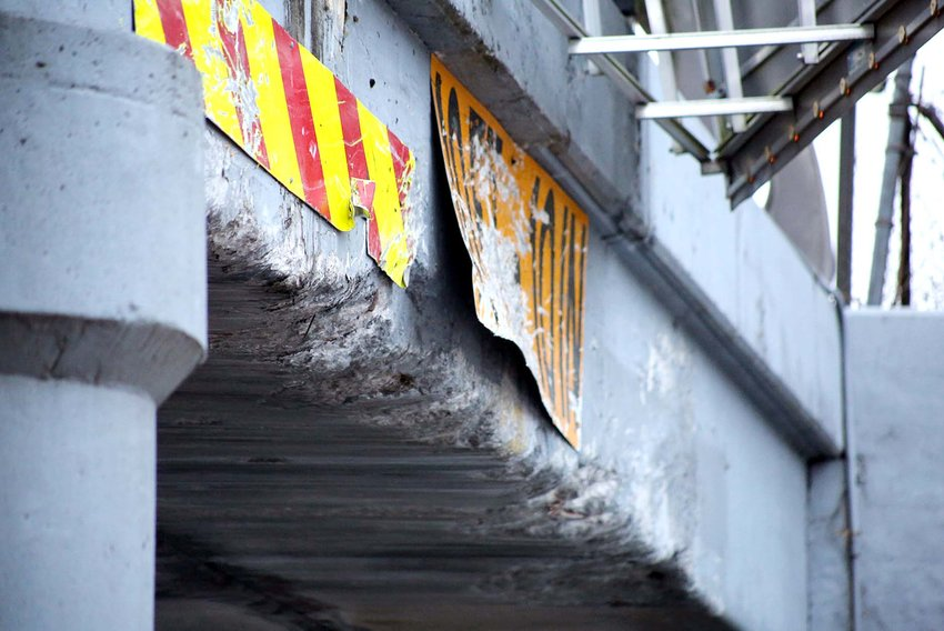 THE BATTLE-SCARRED Inman Street bridge/underpass shows the collective damage caused by a string of collisions involving trucks and other types of high-profile vehicles. The trestle has a 10-foot, 10-inch clearance, and is marked along Inman Street as drivers approach; however, many overestimate the space and underestimate the height of their vehicles. And some apparently don't see the signage.