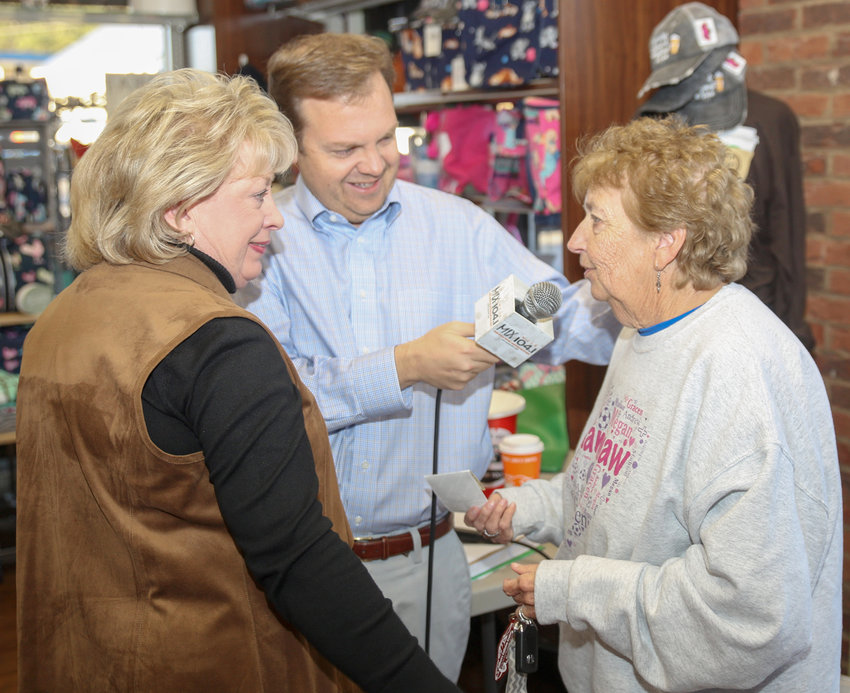 "BECKY SHEAN, right, speaks with Sandra Rowland and Steve Hartline after donating $55 to the Empty Stocking Fund during Thursday morning's live remote at Preferred Cherokee Pharmacy. Shean said  the donation amount represented $10 for each of her grandchildren, as well as $5 she referred to as ""faith money."""