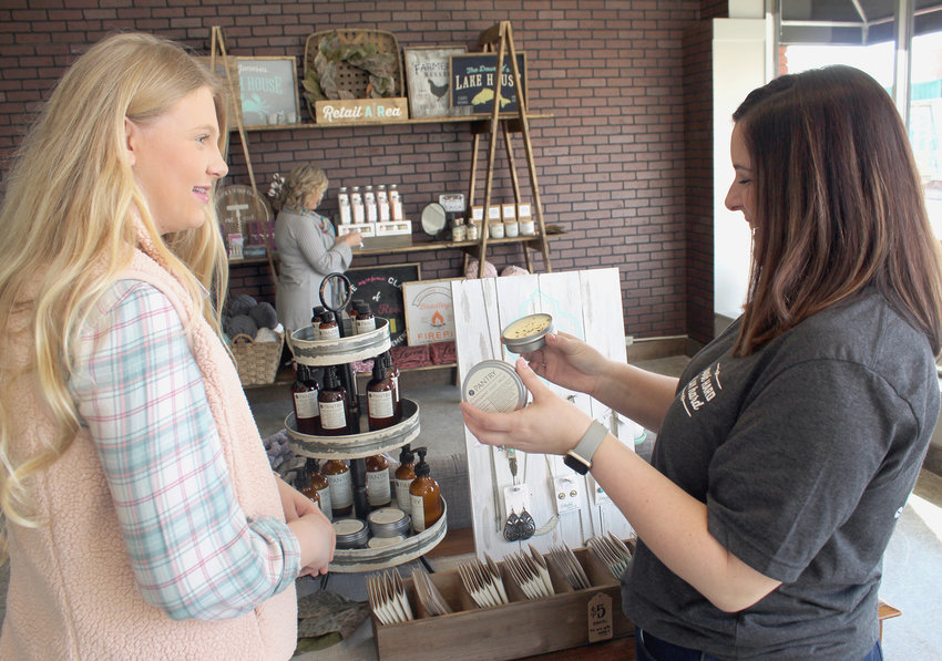 MISTY BROWN, owner of AR Workshop in downtown Cleveland, helps holiday shopper Caroline Phillips select a gift at the art studio. Joel Henderson, communications director for the Cleveland/Bradley Chamber of Commerce, said business was brisk Saturday in downtown Cleveland for Small Business Saturday.