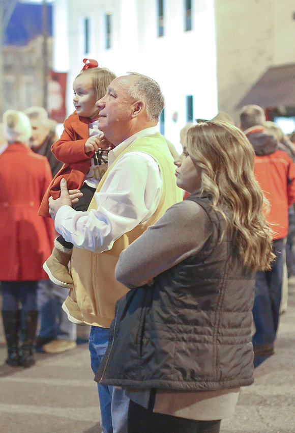 TRUSTEE MIKE SMITH holds his granddaughter, Saylor Harbison, during the lighting of the community Christmas tree. Also shown is Summer Harbison, right.
