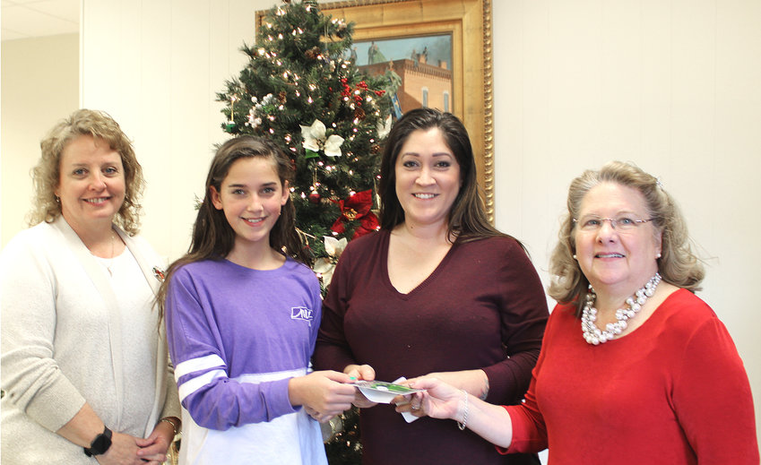SARA ADAIR and her daughter, Sophie Blackburn, claimed their prize Friday in the Cleveland Daily Banner and Merchants' $500 Christmas Cash Giveaway. From left are Banner Sales Representative Kathy Payne; Sophie Blackburn; Sara Adair; and Banner Advertising Director Sheena Meyer.