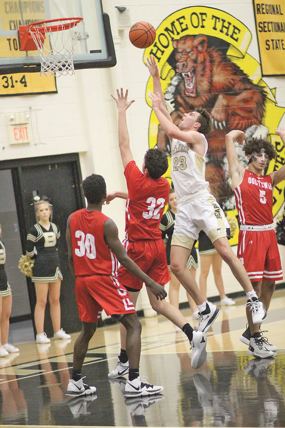 "BRADLEY CENTRAL junior Mason Rothwell (23) puts up a shot over an Ooltewah defender for two of his 15 points in Tuesday evening's Bear victory at ""The Jim."""