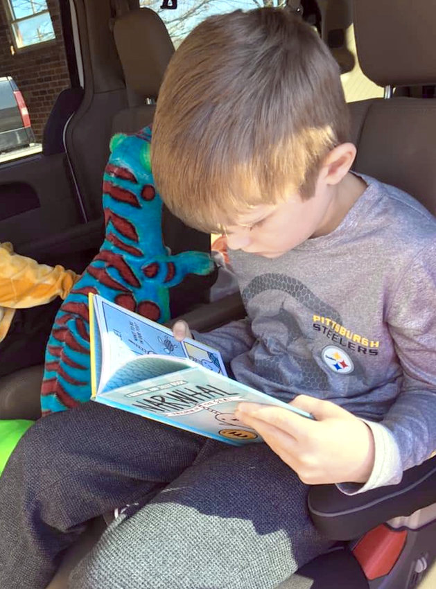 """FIRST-GRADER Jennings Weekley reads """"Narwhal: Unicorn of the Sea"""" to keep up with his Read 20 pledge. Weekley and his brother Andrew practice reading 20 minutes everyday, which netted them the chance to go to a Globetrotters game on Friday."""