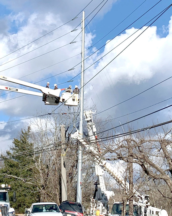 UTILITY WORKERS work to replace a utility pole that was damaged when a vehicle slammed into it Monday morning. The single-vehicle accident resulted non-life threatening injuries to the driver, but knocked out power to hundreds of Cleveland Utilities and Volunteer Energy Cooperative customers.