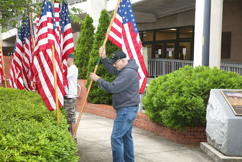 DAVID PENNER slides a flag into place as part of the Memorial Day display of flags in front of the Bradley County Courthouse. Although a public ceremony is not being held this year in tribute to Memorial Day and America's fall soldiers, the flags have still been placed in their traditional downtown spots.