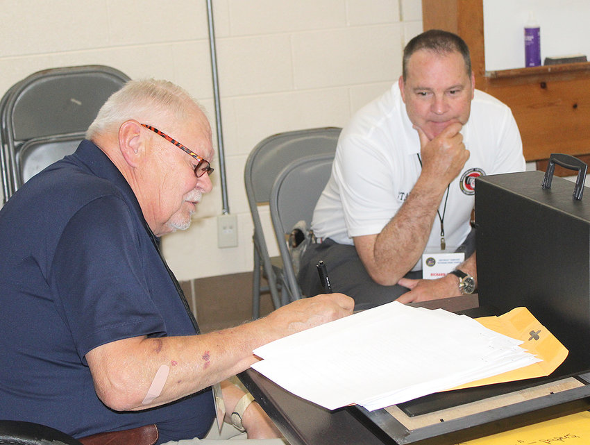 SOUTHEAST TENNESSEE Veterans Home Council Chairman Kim Dees, left, and Council Golf Committee Chair Richard Heinl, review some information between a meeting of the Golf Committee and the council's Executive Committee Thursday afternoon. The meetings were at the National Guard Armory on Dalton Pike.