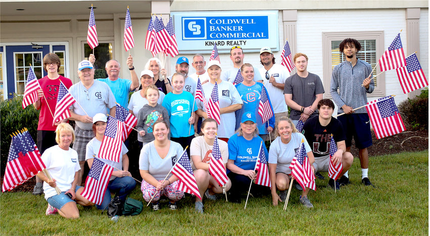 AN EXCITED GROUP of Coldwell Banker Commercial Kinard Realty team members, family members and volunteers painted Cleveland red, white and blue by placing flags along the main thoroughfares of the city on Thursday morning.