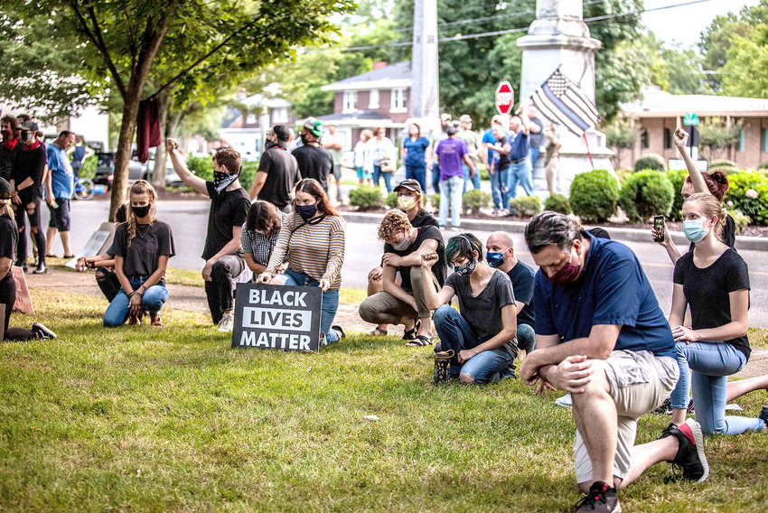 A GOUP OF #EMANCIPATE CLEVELAND members kneel in support of racial justice in the Cleveland and Bradley County community. The group, which is not affiliated with the national Black Lives Matter organization, is comprised of a diverse collection of ages, races, ethnicities, workers and religions, supports moving the Confederate statue from its current location at the junction of Broad, Ocoee and Eighth streets. Pictured in the background are statue supporters who want the monument to remain where it is.