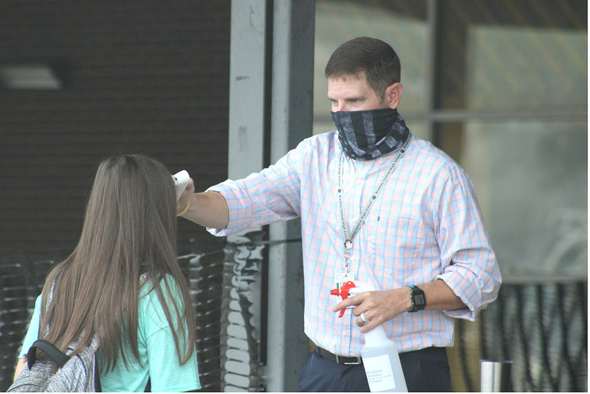 HEALTH SCIENCES teacher Drew German checks the temperature of a Bradley Central High School student before school on Friday.