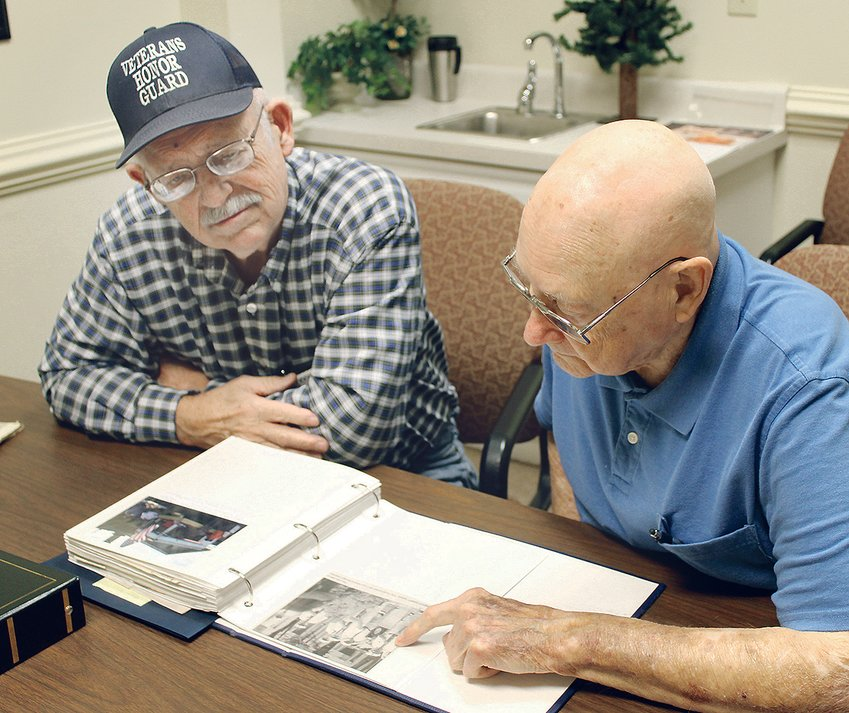 CARL ZURCHER, right, and John Thomason look over some photographs of the Bradley County Veterans Funeral Honor Guard in a visit to the offices of the Cleveland Daily Banner last year.