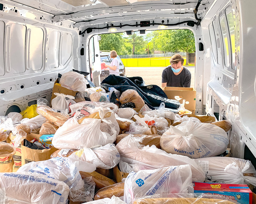 A VOLUNTEER of The Caring Place readies bags of food within the Community Cares Mobile Pantry.