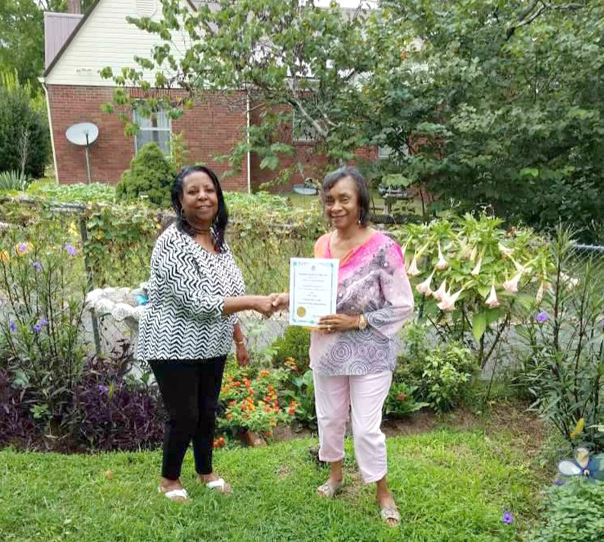 Charlotte Scott, president, presents a Certificate of Commendation from The National Garden Clubs, Inc., to Cynthia Humes, who won first place in the Conservation Education category.