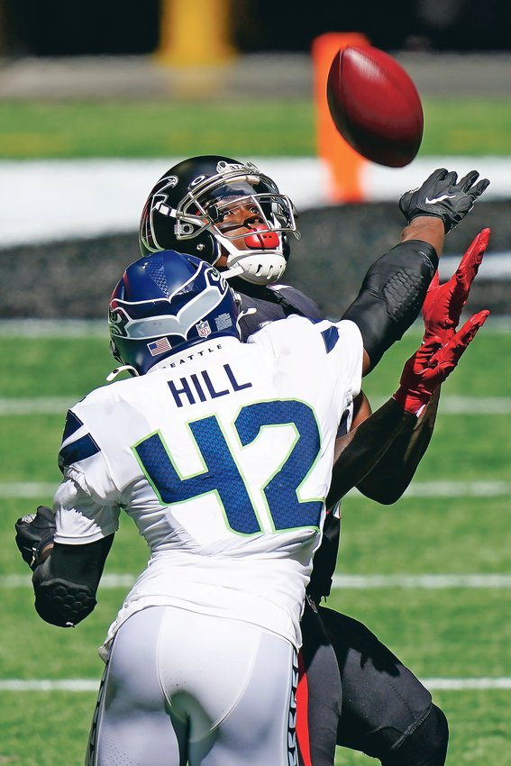 ATLANTA FALCONS' wide receiver Julio Jones (11) makes a catch against Seattle Seahawks safety Lano Hill (42) in the second half Sunday, in Atlanta.