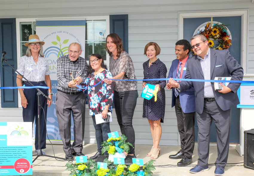VINCENTE AND AURELIA RODRIGUEZ, center, cut the ceremonial ribbon on their new home. From left are Fran Henry, Vincente and Aurelia, Tammy Johnson, Cathy Barrett, Rogelio Lantigua and Pastor Miguel Vega.