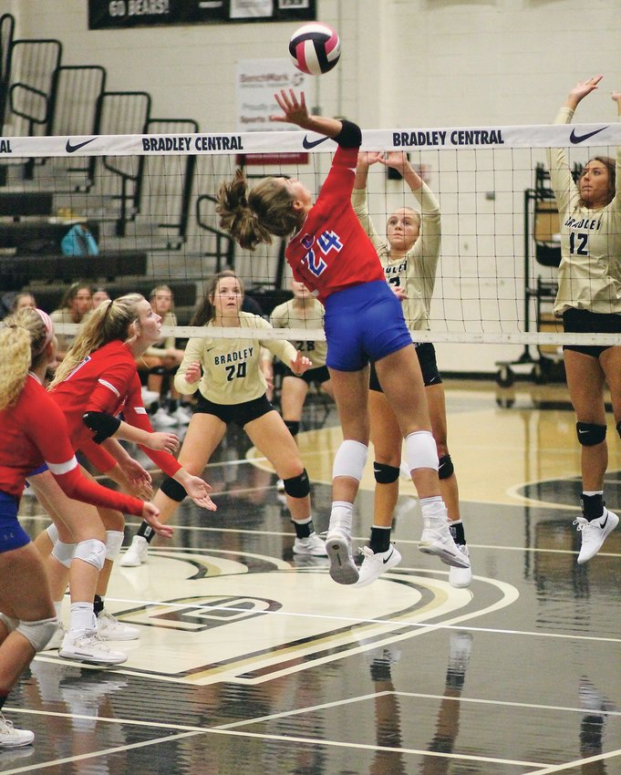 CLEVELAND HIGH senior Addison Hurst (24) powers one of her dozen kills, while teammates Joy Douglass and Kinslee McGowan look on and Bradley Central's Kelsey Carman (23), Ashlan Crittenden (center) and Callie Elrod (12) try to defend, during Thursday evening's District 5-AAA action at Jim Smiddy Arena.