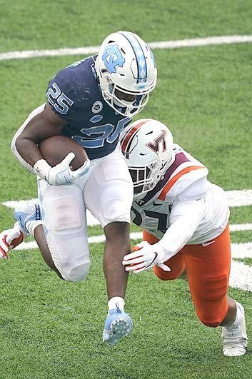 VIRGINIA TECH linebacker Rayshard Ashby chases North Carolina running back Javonte Williams (25) in the first half Saturday, in Chapel Hill, N.C.