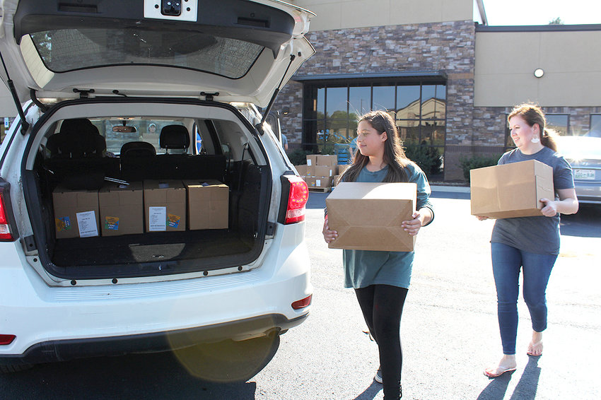 VOLUNTEERS at Westmore Church of God carry USDA Farmers to Families food boxes to a waiting vehicle, during a distribution earlier this month.