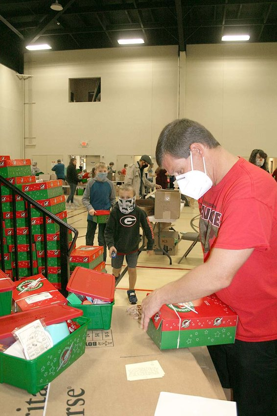HEATH MOODY closes and secures the shoeboxes of gifts.