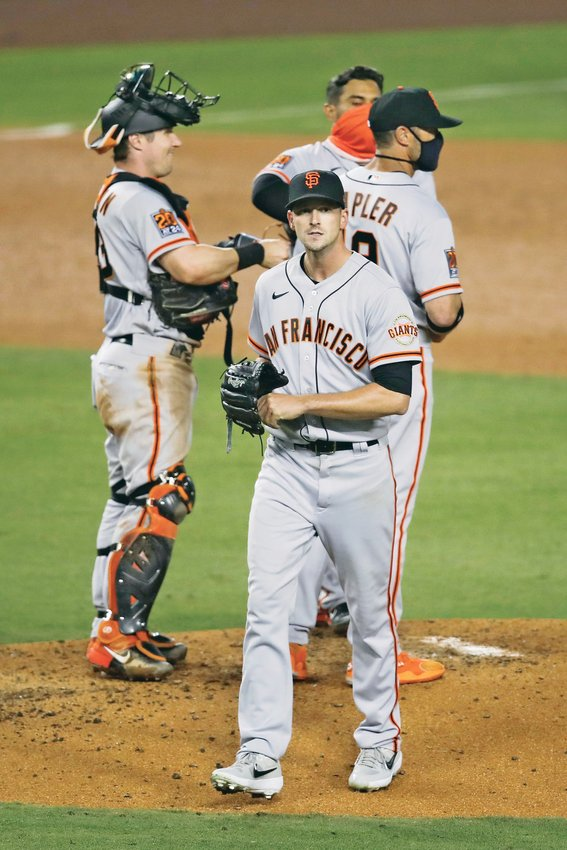 SAN FRANCISCO GIANTS starting pitcher Drew Smyly, center, leaves the mound after being relieved in the fourth inning against the Los Angeles Dodgers, July 26, in Los Angeles.