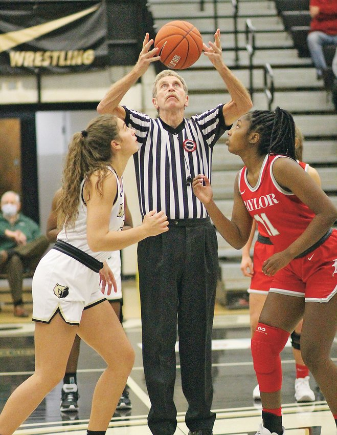 """LOCAL REFEREE Larry Osborne, center, tosses up the new prep hoop season's first tip-off Tuesday evening between Lee University signee Anna Mohonen, left, and Wake Forest commit Raegyn Conley (11). """"Defending"""" state champion Bradley Central blew out Baylor 71-37 at """"The Jim."""""""