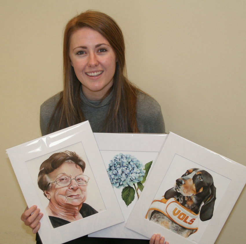 GRACE MANNING holds three of her paintings. One is a portrait of a woman, a blue hydrangea and of Smoky, the UTK mascot.