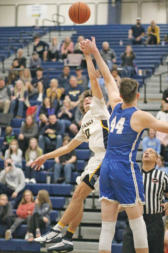 """WALKER VALLEY's 6-foot senior Hayden Moore (10) knocks the opening tip away from McCallie's 7-foot-2 David Craig in Tuesday evening's 66-59 Mustang victory, at """"The Stable."""""""