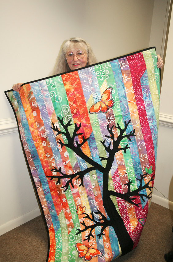 """JACKIE CORY holds up her a colorful quilt, complete with tree, butterfly and """"jelly roll"""" strips. The reversible quilt features a Thanksgiving top on the other side"""