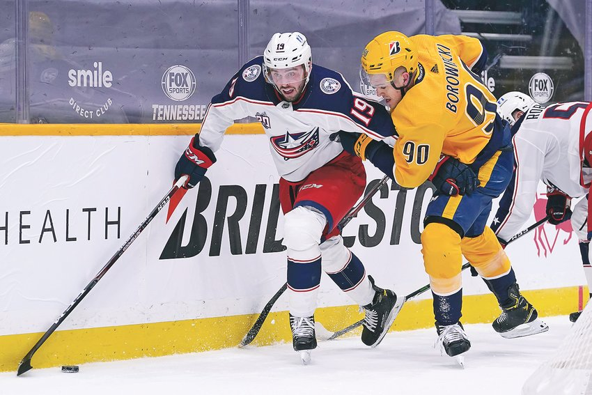 NASHVILLE PREDATORS defenseman Mark Borowiecki (90) and Columbus Blue Jackets center Liam Foudy (19) battle for the puck in the first period Thursday, in Nashville.