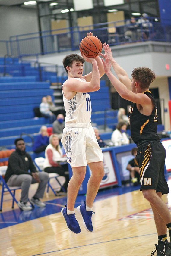 CLEVELAND SENIOR GUARD Grant Hurst (11) puts up a shot in the first quarter against McMinn County Tuesday, inside The Raider Dome.
