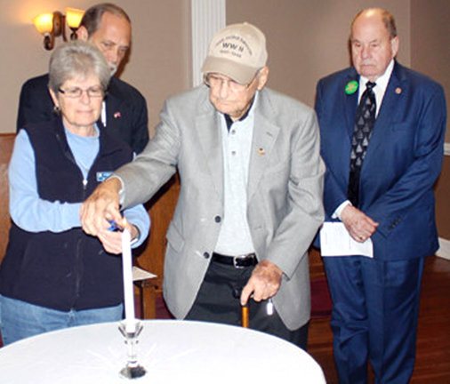 WHILE HIS WANING HEALTH still allowed it, George Allen attended Pearl Harbor Remembrance Day events at the Elks Lodge. Here, with the help of his daughter Janet, he lights a memorial candle. In the background are Bradley County Mayor D. Gary Davis and former Cleveland Mayor Tom Rowland.