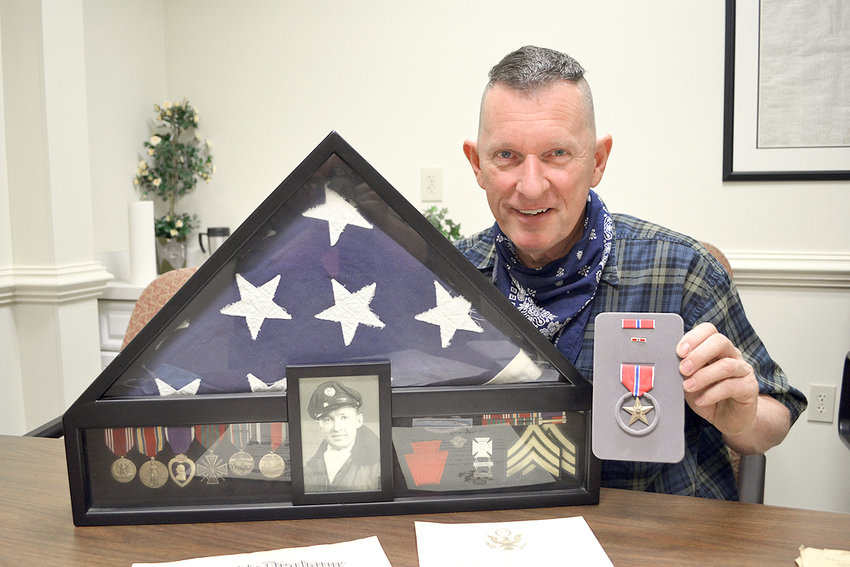 DWIGHT REAGAN holds the Bronze Star   he recently received honoring his father, Blane, who served in the U.S. Army during World War II. Reagan had been seeking that medal since learning his father should have received it for his service as an ammunitions handler and Combat Infantry Badge, which is among the medals in the shadow box he is holding.