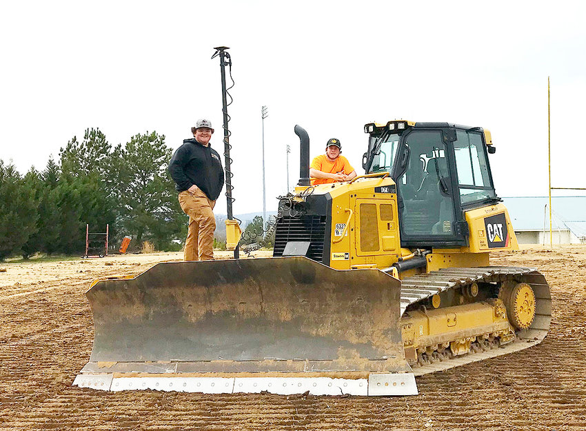 BRADLEY COUNTY students Dyllan Jenkins and Preston Lawson stand on a bulldozer they used to fix the Walker Valley High School football practice field during their spring break.