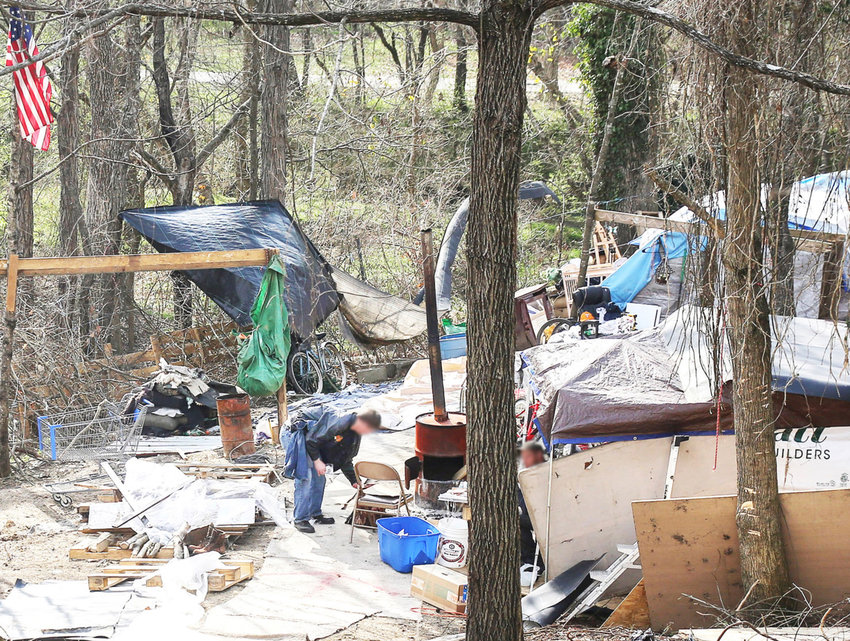 A MAN living in an encampment located between a retail strip center and Mouse Creek, moves items near a carpeted pathway. Approximately five men live in tents at the site.
