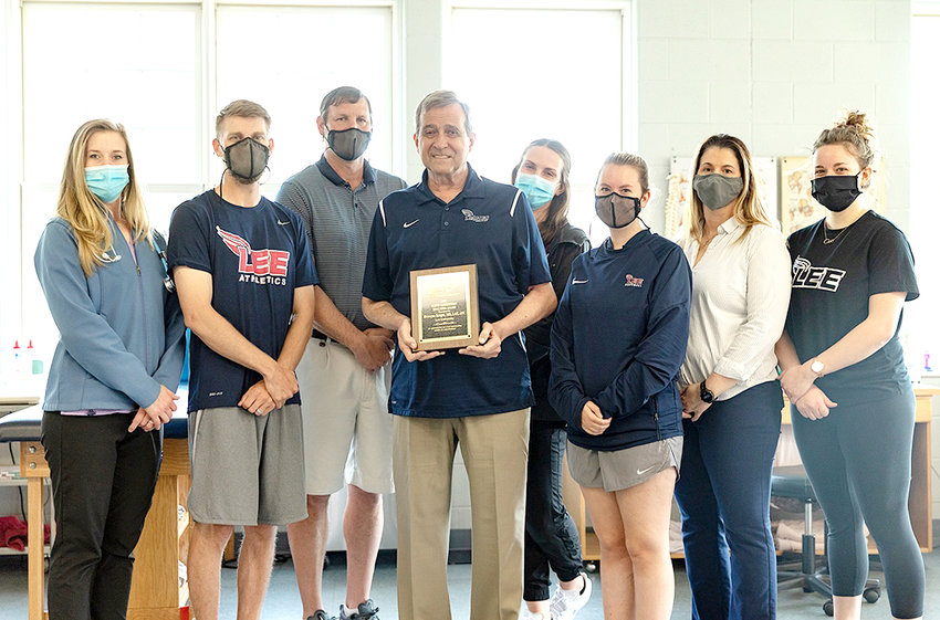 Dr. Dewayne Knight, holds his Jerry Robertson Educator of the Year Award, with the Lee University athletic training team, from left, Breanne Crittenden, Dan Heinbaugh, Jeff Mullins, Knight, Maddie Kalke, Shelby Landlot, Assistant Professor of Athletic Training Dr. Racheal Lawler, and Gabby Mammano. (Not available for photo was Dr. Taz Kicklighter.