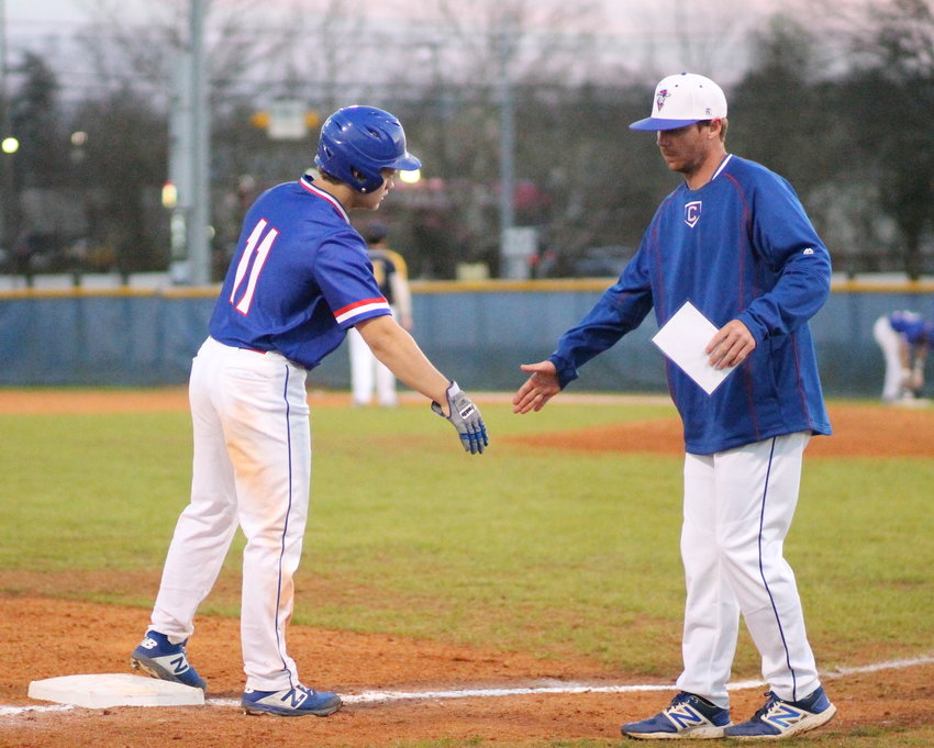 MILLIGAN COMMIT Ethan Jones, left, is greeted by Clevleand head coach Preston Scoggins. The senior Blue raider catcher reached base four times in Monday evening 's 11-6 CHS victory over McMinn County, in Athens.