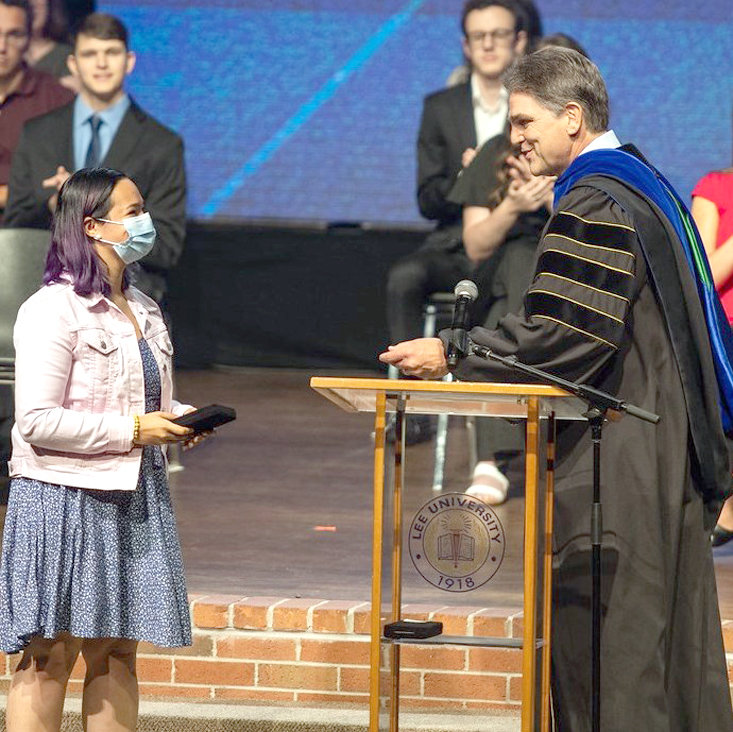 LEE UNIVERSITY President Dr. Mark Walker, right, presents Grace Ann Cochrane the Zeno C. Tharp Award during a special Honors Chapel this month. Lee's Cochrane receives Tharp Award