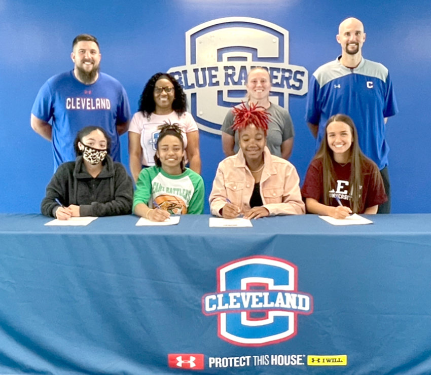 FOUR CLEVELAND LADY RAIDERS signed scholarships this week to play basketball at the collegiate level. From left, Mariyah Person, Chattanooga State; Jamaryn Blair, Florida A&M; Jadyn Chestnutt, Langston (Okla.) University; and Kara Williams, Lee University. Standing, from left, are CHS coaches Jaime Baird, Anne Person, Dawn Barger and Tony Williams.