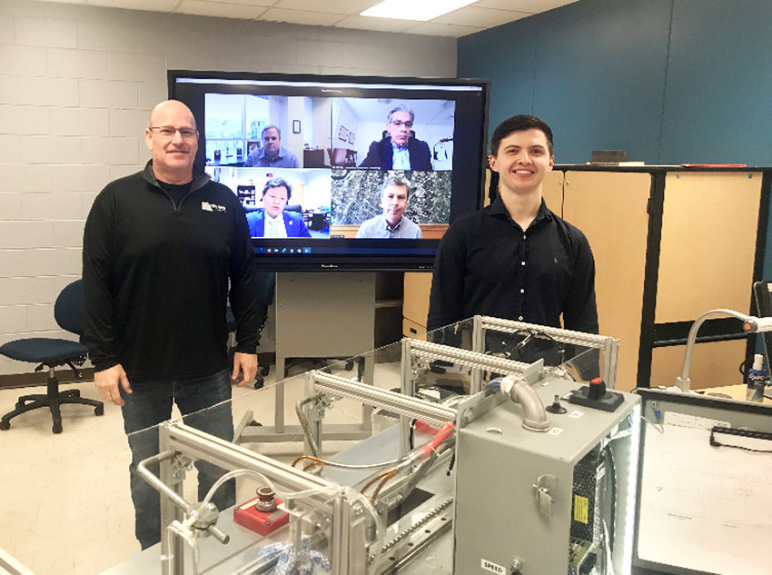 RODGER HILL, left, and Zach Presley, right, two graduates of CSCC's Mechatronics Engineering Technology program, took home first place in design at the recent 2021 UTC Technology Symposium for their automated car wash system project. The former CSCC students won a trophy and a cash prize. They are both employed with Triumph Sheets of Cleveland. Hill and Presley stand with their spring 2020 capstone engineering project featured in the showcase.