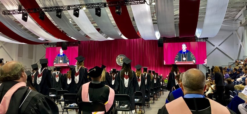 GRADUATES STAND as their degrees are conferred in the first ceremony at Lee University held since December 2019 due to the coronavirus pandemic.