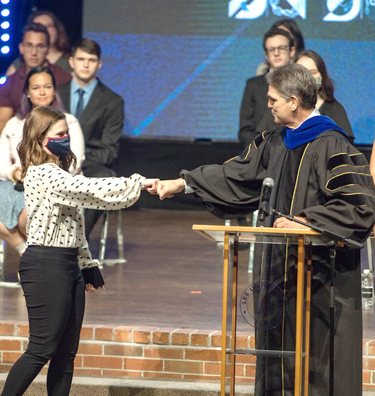 Lee President Dr. Mark Walker, right, congratulates Desiree LaPeer with a fist bump during a recent chapel service where she was awarded the CPC Award.
