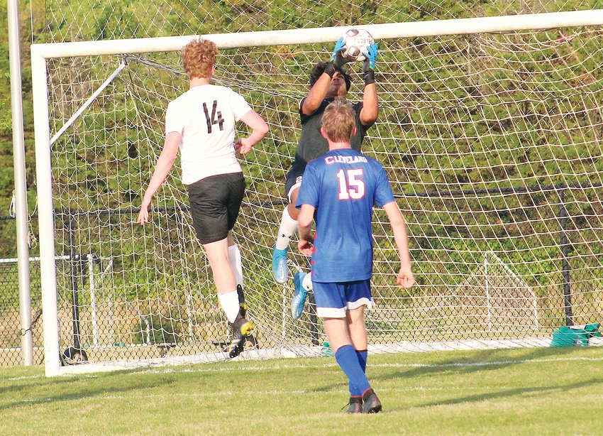CLEVELAND GOAL KEEPER Andres Rodas, back, makes a stop in the first half against McMinn County in the first half of a District 5-AAA soccer semifinal match Tuesday, at the GCSC.