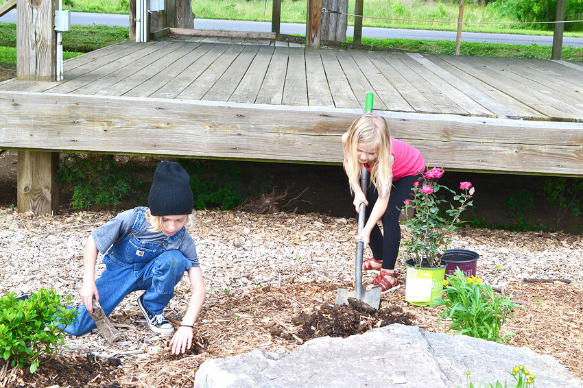 GRAHAM AND INDIE HAMMONTREE help plant flowers along the front of the stage at the Charleston Park in anticipation of attendees for the upcoming Tractor Show and other events at the park.