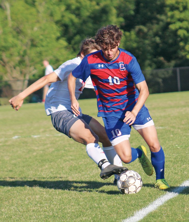 CLEVELAND MIDFIELDER Lawson Dale (10) battles an Ooltewah defender in the first half of the District 5-AAA championship game Thursday, at the Greater Cleveland Soccer Complex.